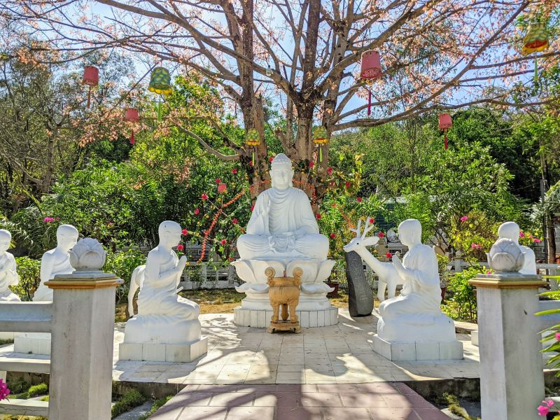 Five white monks statues nearl on their knees while a white Buddha statue looks forward at a pagoda on Nui Dinh Mountain, Vietnam