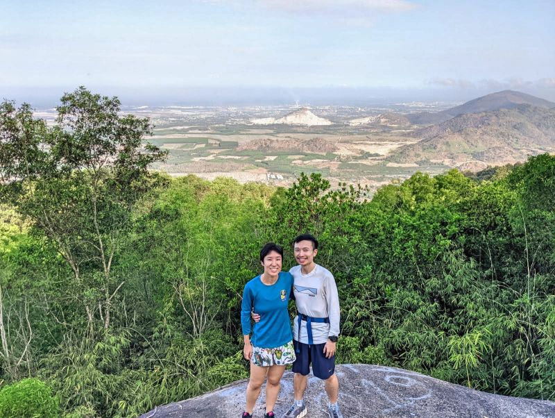 Jackie Szeto and Justin Huynh, Life Of Doing, stand on a rock with the overview of Ba Ria-Vung Tau area on Nui Dinh Mountain, Vietnam