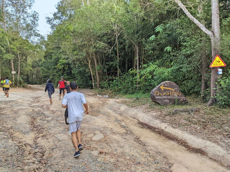 Groups of runner along the dirt path veering left to the temple route at Nui Dinh Mountain.