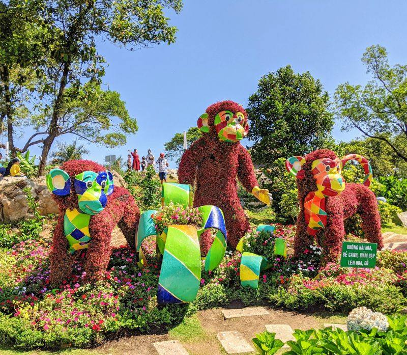 Three monkeys with colorful mosaic faces made out of red plants and flowers at Sun World Ba Den in Tay Ninh, Vietnam