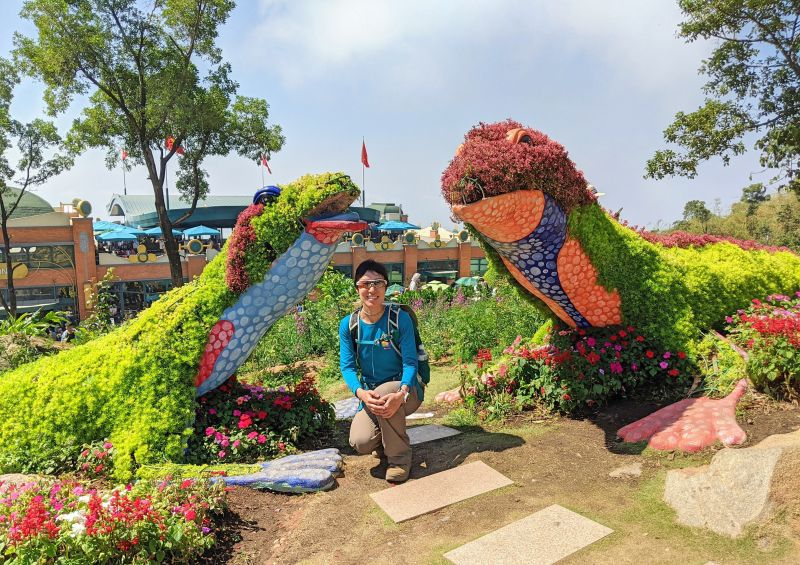 Jackie Szeto, Life Of Doing, pose underneath two lizard topiaries made out of green and red plants at Sun World Ba Den in Vietnam