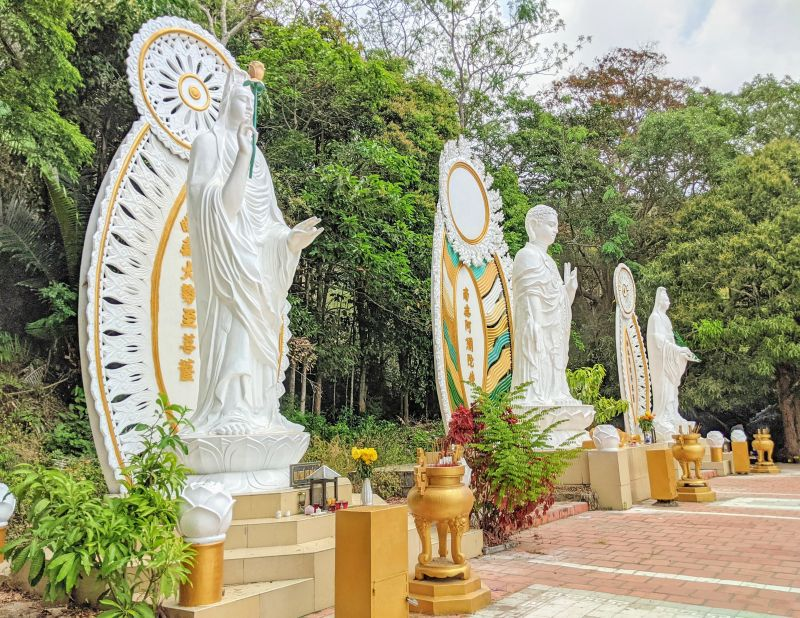 Three white Buddha statues and each with a praying area
