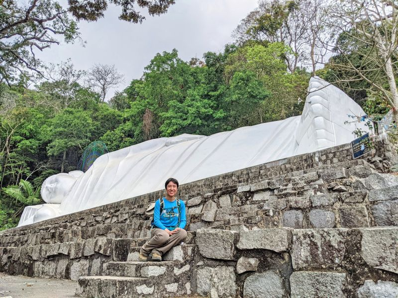 Jackie Szeto, Life Of Doing, poses in front of the white reclining Buddha at Ta Cu Mountain, Vietnam