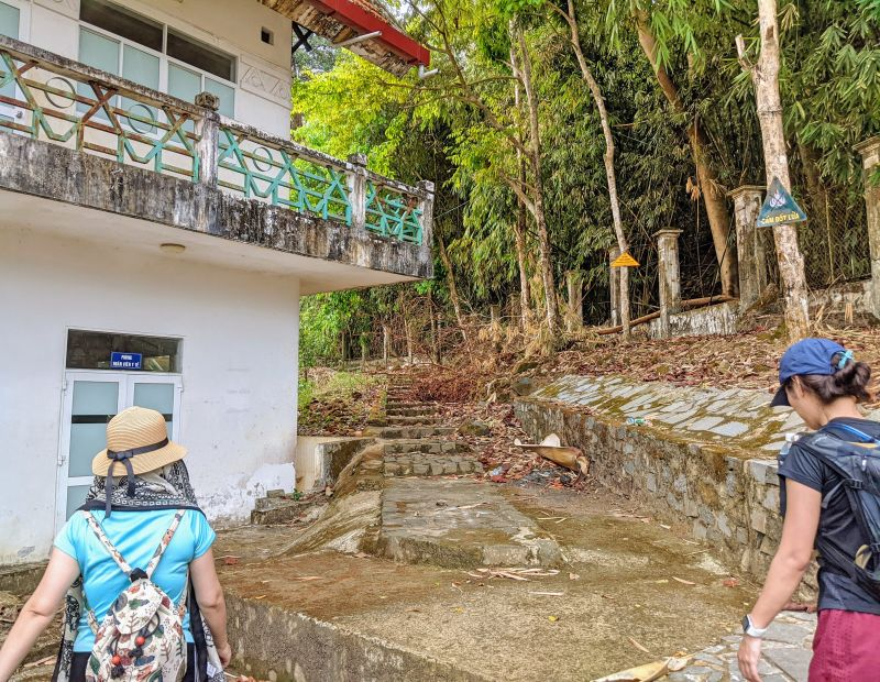 Two female hikers walk towards the stone staircase to start the Ba Ra Mountain hike in Binh Phuoc, Vietnam