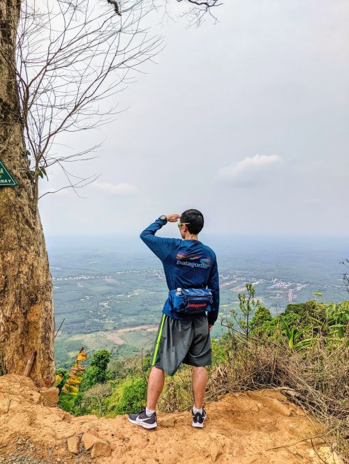 Justin Huynh, Life Of Doing, has his hand to his forehead and looking over the Binh Phuoc lands from the edge of the Ba Ra Mountain, Vietnam