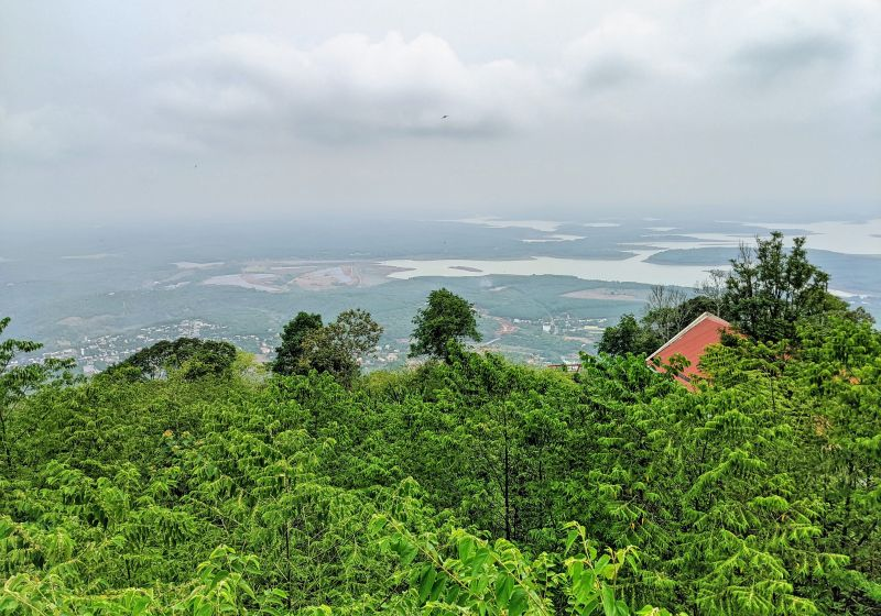 An aerial view of Binh Phuoc's forest area, lakes, and trees from Ba Ra Mountain hiking trail in Vietnam