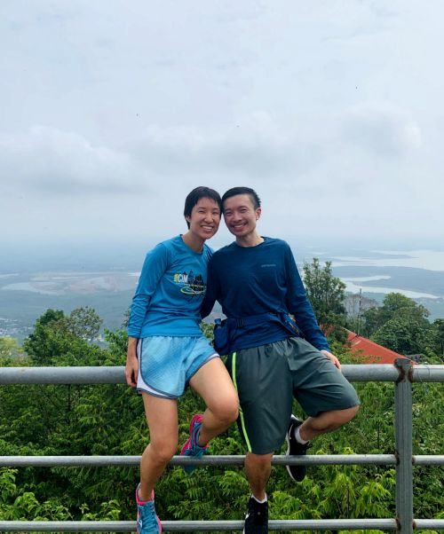 Jackie Szeto and Justin Huynh, Life Of Doing, at the summit of Nui Ba Ra with the view of Binh Phuoc area in the background.