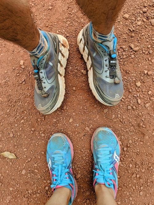 An aerial view of a pair of black and blue Hoka running shoes and a pair of pink and baby blue Saucony running shoes on the red clay dirt trail in Ma Da Forest, Vietnam