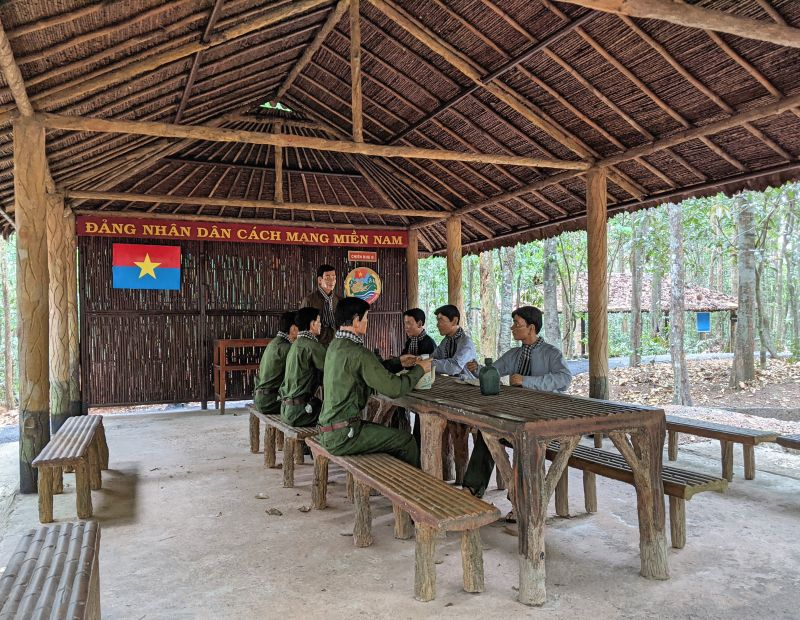 Replica of 7 soldiers and 1 leader of the Vietnamese army having a discussion under a straw covered hut in Ma Da's Southeast Commissioners Area Ruins.