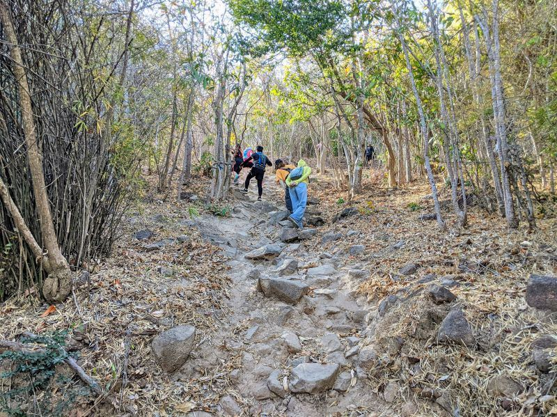 Four hikers walking up the rocks of the Nui Lon hiking trail in Vung Tau, Vietnam
