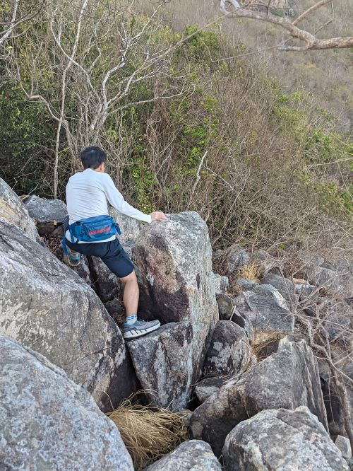 Justin Huynh, Life Of Doing, climbs down the giant grey rocks to continue on the Big Mountain Vung Tau hiking trail.
