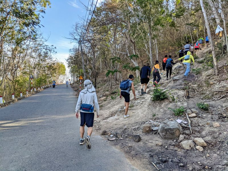 Justin Huynh, Life Of Doing, and a dozen hikers start the Nui Lon Big Mountain hiking trail from the road in Vung Tau, Vietnam