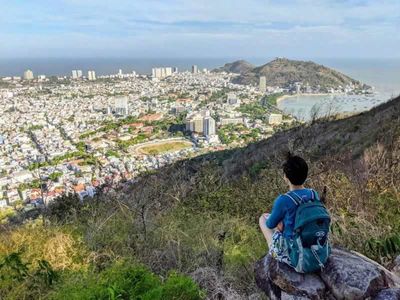 Jackie Szeto, Life Of Doing, sits on a rock and looks at the beautiful views of Vung Tau city and the bay on Nui Lon Big Mountain in Vietnam