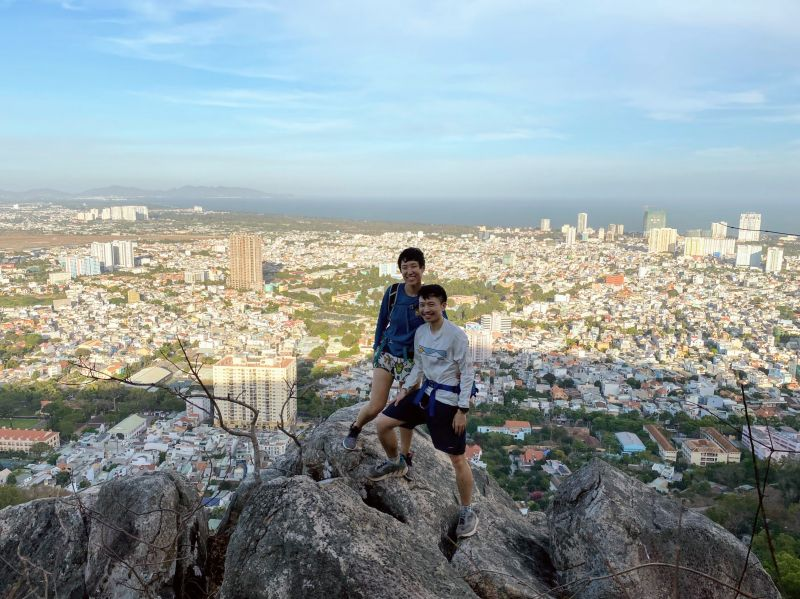 Justin Huynh and Jackie Szeto, Life Of Doing, stand on a rock with the Vung Tau City and buildings in the background on Nui Lon Big Mountain, Vietnam