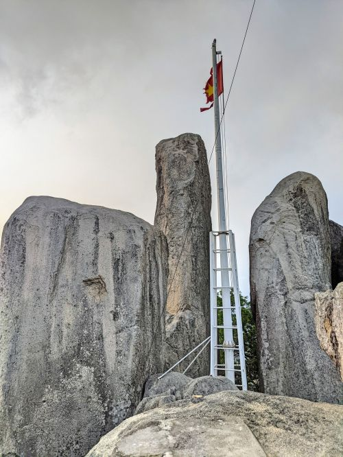 A flagpole with a Vietnamese flag is perched on top of grey rocks on Nui Minh Dam Mountain.
