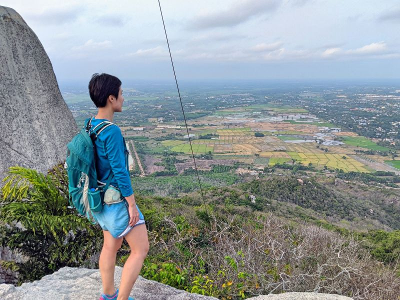 Jackie Szeto, Life Of Doing, stand on a rock with the view of yellow and green farmlands from the top of Minh Dam Mountain near Vung Tau, Vietnam