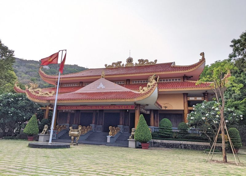 A building with a red roof and golden dragons in the Historical Relic area of Minh Dam.