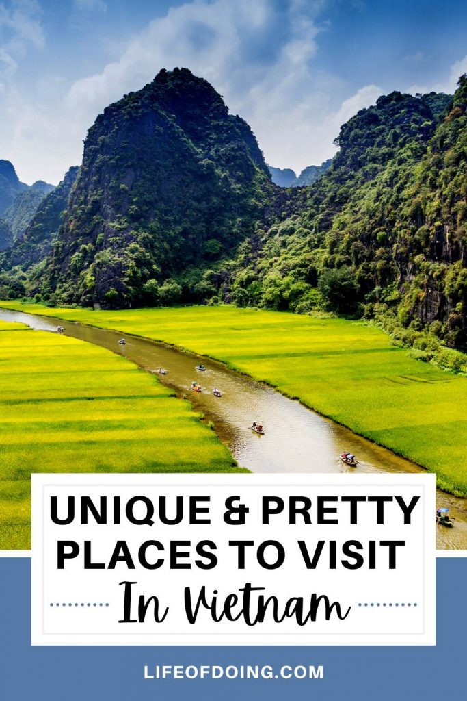 A river flows between two green fields in Ninh Binh, a beautiful spot to visit in Vietnam