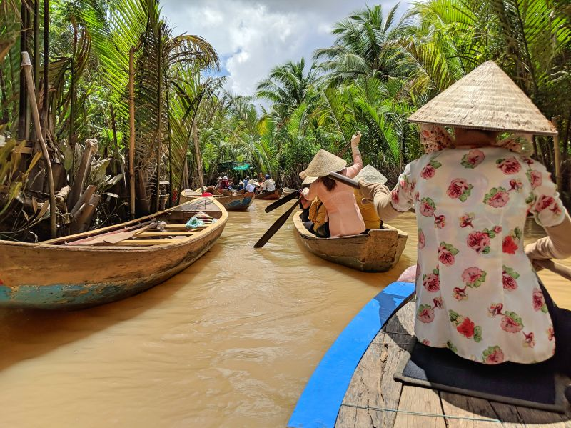 Rowers wearing conical hats row their wooden sampan boats ride along Ben Tre, one of the top places to visit in Vietnam's Mekong Delta.