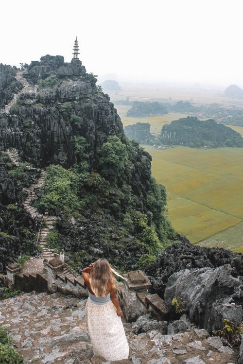 A blonde woman wears a white dress and is walking along the stairs with the Hang Mua viewpoint in Ninh Binh, Vietnam