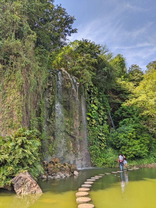A couple stand on a walking stone next to a waterfall at Buu Long Theme Park in Bien Hoa, Dong Nai Province, Vietnam