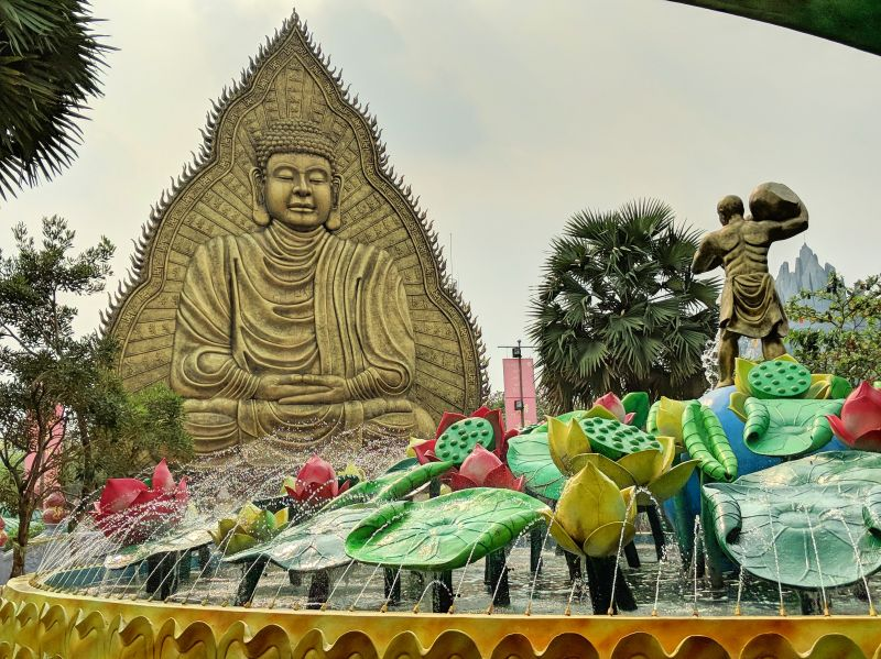A bronze Buddha statue in front of a lotus water fountain at Suoi Tien Theme Park in Ho Chi Minh City, Vietnam