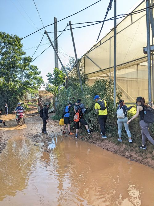 Six people hang on to the fence and walk on a narrow dirt path to bypass the muddy and flooded road.