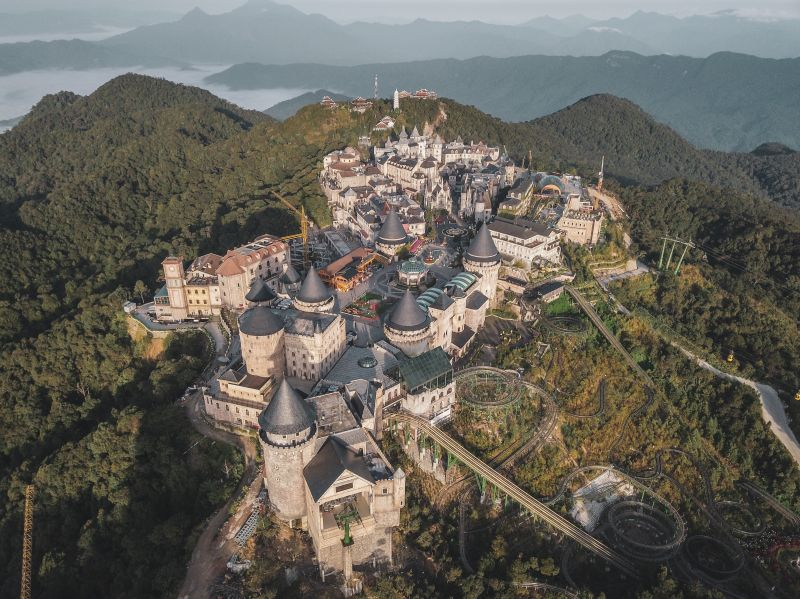Aerial view of castles and European-inspired buildings on top of a mountain at Sun World Ba Na Hills Theme Park in Vietnam