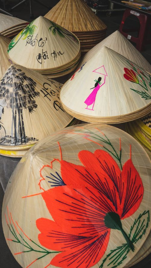 Vietnamese conical hats with various embroidered designs such as red flowers and women in ao dai, Vietnamese outfits.