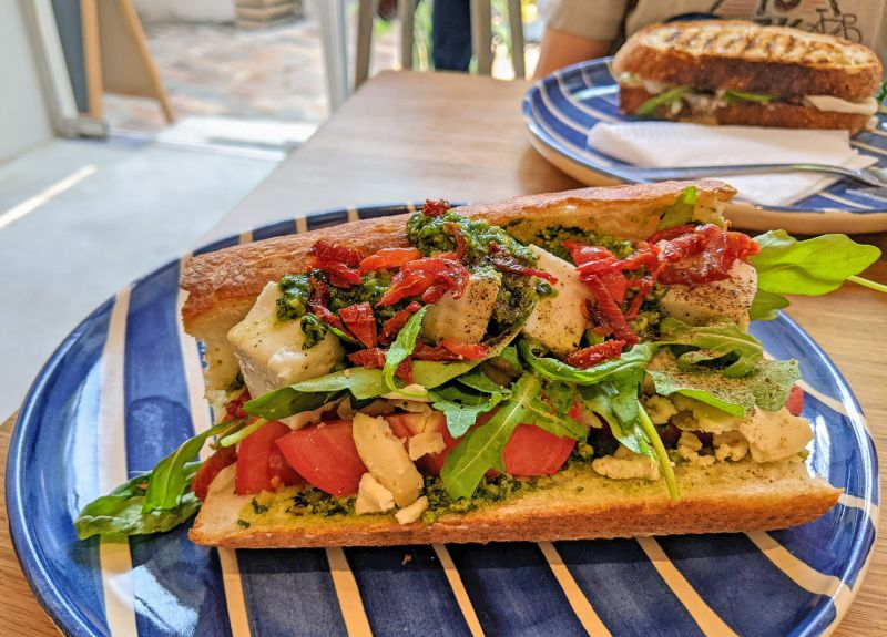 Vegan baguette sandwich with cheese made from cashews, arugula, tomatoes, and pesto from Kashew Cheese in Ho Chi Minh City