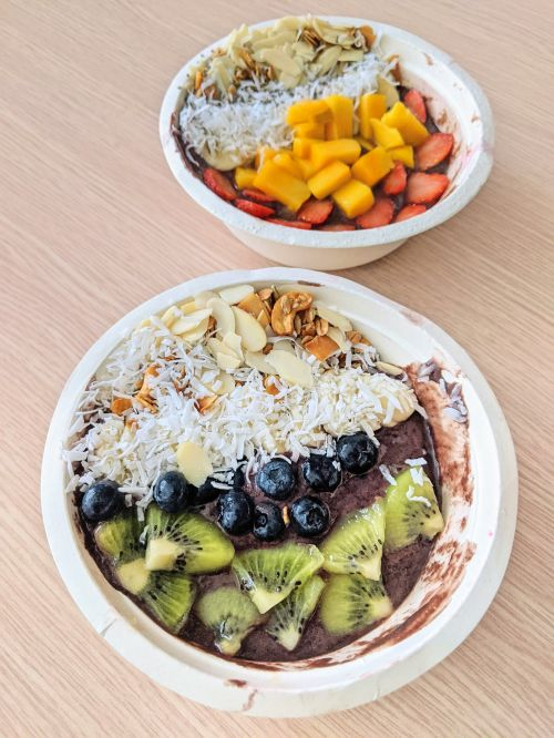 Two bowls with acai, fresh fruits of kiwi, blueberries, mango, strawberries, coconut shavings, and sliced almonds from Pure Bowl in Ho Chi Minh City, Vietnam