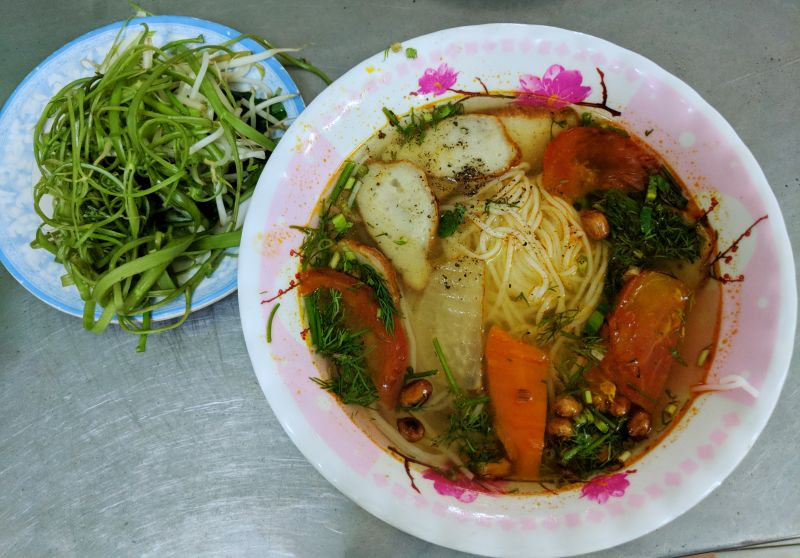 Vegan rice noodles with tofu, dill, and tomatoes and plate of veggies at a local vegan restaurant in Ho Chi Minh City, Vietnam