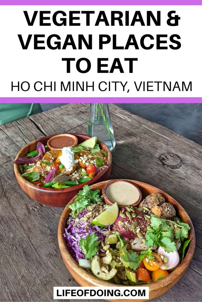 Two colorful salads in wooden bowls on top of a wooden table at a vegetarian and vegan restaurant in Ho Chi Minh City, Vietnam