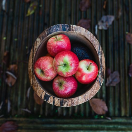 A wooden basket filled with five red apples