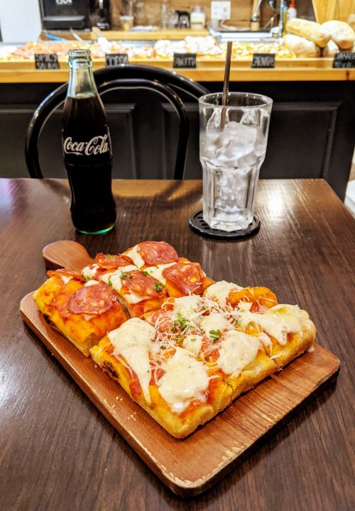 Two square pizzas - spicy salami and mushroom and coppa ham - and a bottle of Coca-Cola from Oliver's Pizza in Ho Chi Minh City, Vietnam