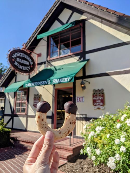 A hand holding up an almond marzipan horn cookie in front of Mortensen's Bakery in Solvang, California