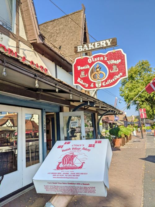 A hand holding up a box of Olsen's Danish Village Bakery cookies in front of the storefront in Solvang, California