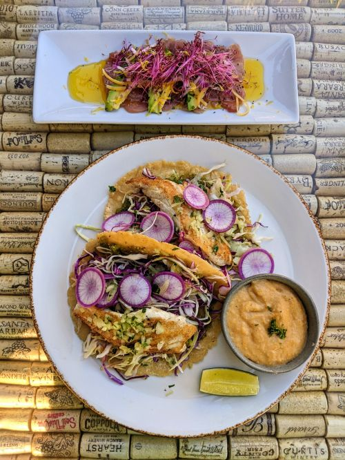 One plate of yellowtail sashimi and another plate of fish tacos at Peasant Feast in Solvang, California