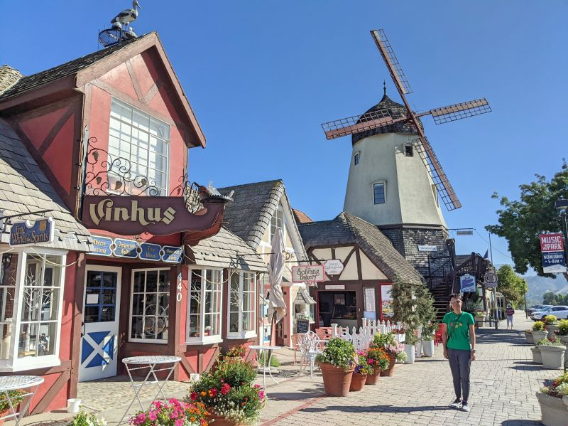 Jackie Szeto, Life Of Doing, stands in front of a windmill in Solvang, California
