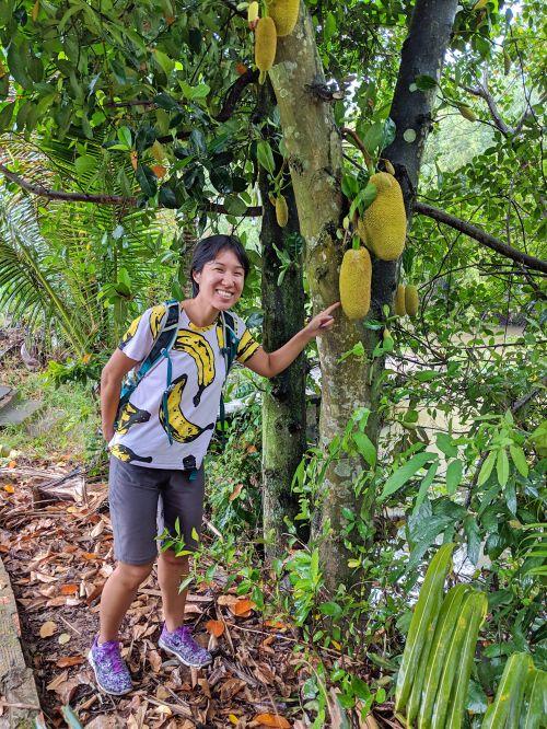 Jackie Szeto, Life Of Doing, stands next to a jackfruit tree in Vietnam.