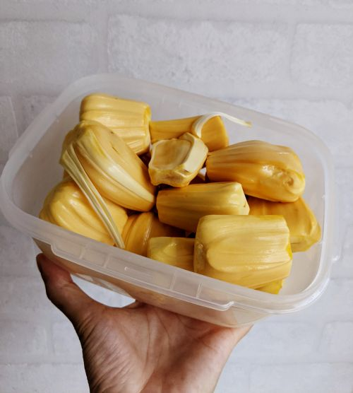 A plastic container of yellow jackfruit already peeled and ready to eat.