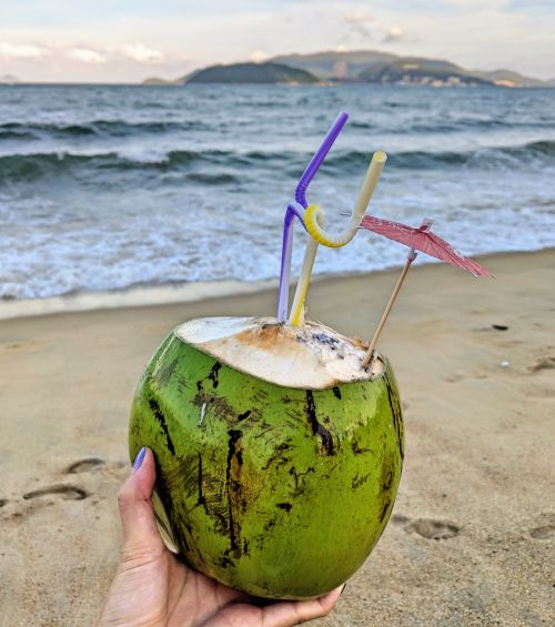 A hand holding a fresh coconut with twisty straws and an umbrella at a beach
