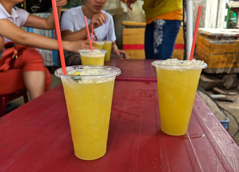 Three cups of iced sugarcane juice with kumquat on a red table