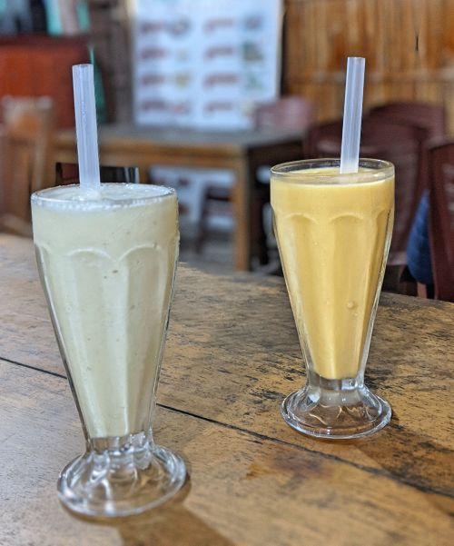 Two cups of fruit smoothies - coconut and mango smoothie - on a wooden table