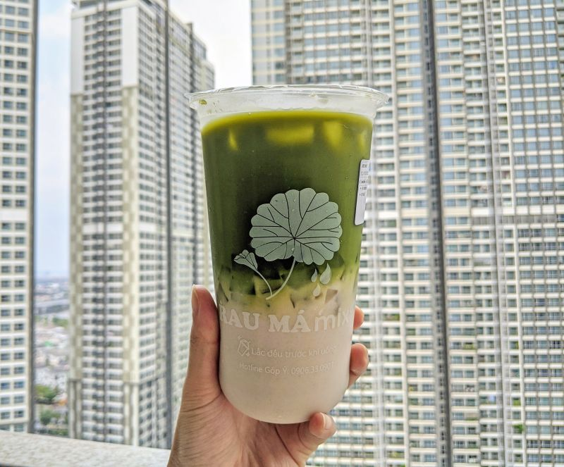 A hand holding up a cup of green juice made from pennywort leaves and coconut milk with jellies.
