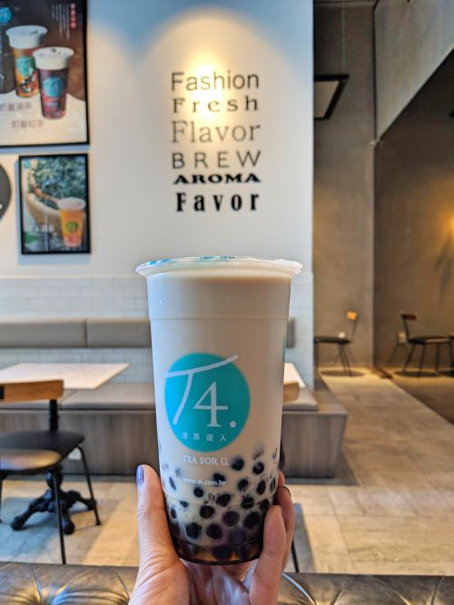 A hand holding a cup of bubble milk tea with black boba pearls from T4 Tea For U in Ho Chi Minh City, Vietnam